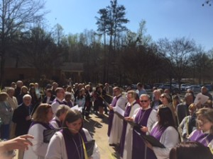 The congregation gathers outside for Palm Sunday worship.